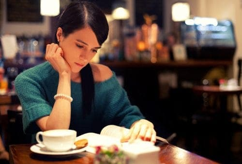Lady reading a book in a coffee shop